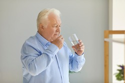 Serious senior man taking medical pills with a glass of fresh water at home. White-haired mature man lives independently and takes prescribed medicine regularly
