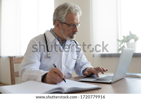 Serious senior mature physician using computer app making notes in medical journal. Older adult doctor therapist consulting remote patient online by video call, watching healthcare webinar training.