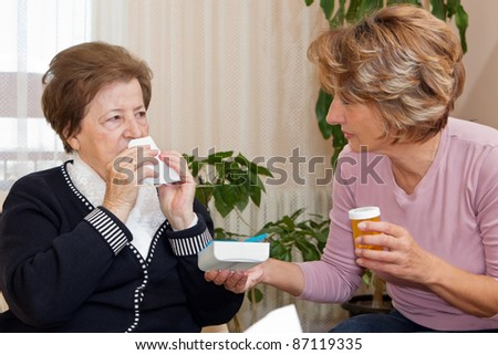 Serious senior woman blowing nose with handkerchief while a nurse giving to her the medicine.