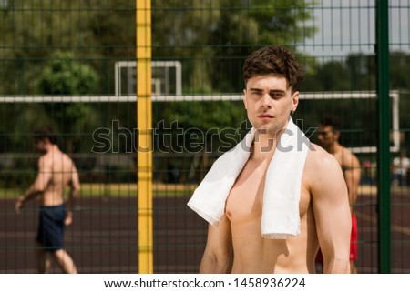 serious shirtless sportsman with white towel standing at basketball court and looking at camera