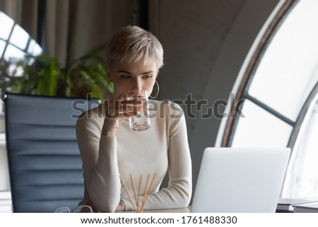 Serious short-haired blond business woman holding glass drinking water looking at pc screen read email take break reduces thirst, prevent dehydration caring about health during workday at workplace