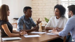 Serious skilled african american young manager explaining market research results to concentrated mixed race teammates. Focused diverse employees listening to biracial colleague at meeting in office.