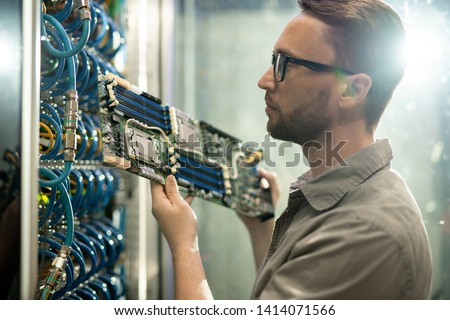Serious skilled young bearded server installation specialist in glasses holding circuit board and examining server racks while working in datacenter room #1414071566