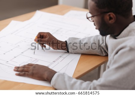 Serious smart engineer drawing a plan