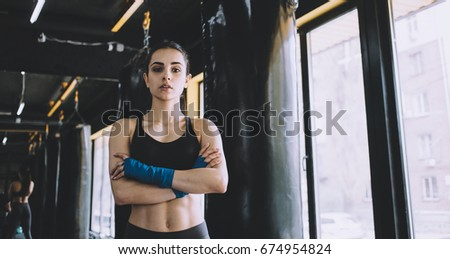 Serious smiling woman standing with crossed arms in the gym near the window, Sporty girl has wrapped her fists with blue cloth. Close up Stock foto ©