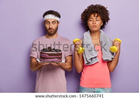 Serious sporty woman trains with dumbbells, has good willpower, looks at baked cake in mans hands, doesnt eat junk sweet food leads healthy lifestyle. Sportsman stares with temptation at tasty dessert