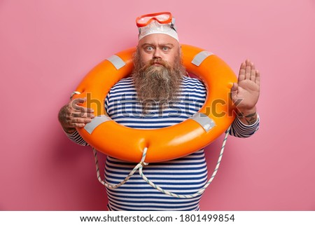 Serious stout man has thick beard makes no gesture, has safety beach holiday, poses with inflated lifering, wears striped sailor shirt, isolated on pink background. Swimming time, summer concept Stok fotoğraf ©