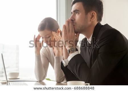 Serious stressed businessman thinking hard how to solve problem while worried businesswoman trying to concentrate, preparing to important negotiations, facing business challenge, company bankruptcy