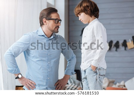 Serious strict man looking at his son #576181510