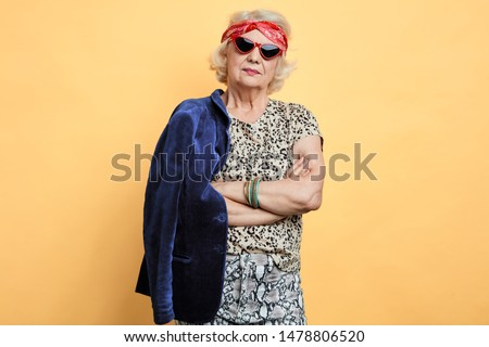 serious strict old woman with crossed arms looking at the camera. studio shot. #1478806520