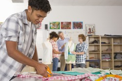 Serious student cutting fabric in home economics classroom