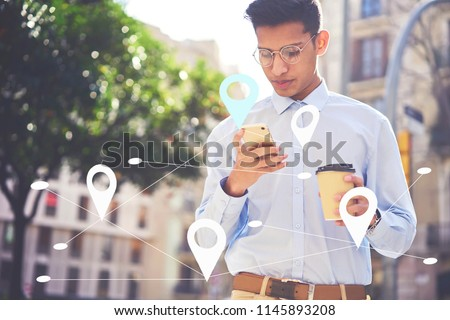 Serious student sending messages to friends in social network. Young male searching via app food restaurants near his location. Maps application for smartphone. Infographics tags with virtual map