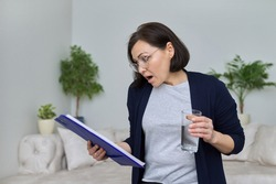 Serious surprised mature business woman with glasses with a glass of water reading paper files