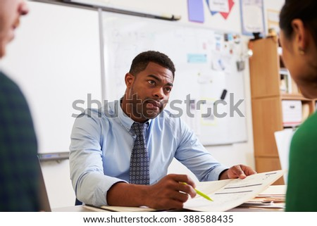 Serious teacher at desk talking to adult education students