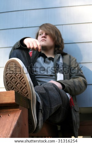 stock photo : Serious teenage boy sitting on a railing outdoors in winter, ...