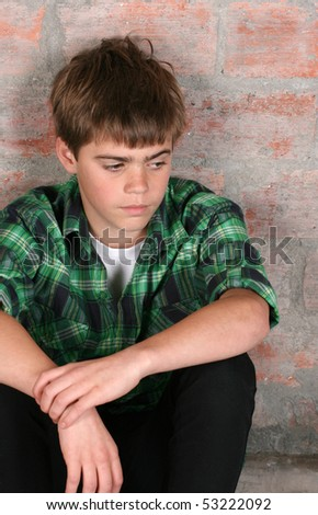 Serious teenager sitting alone against a brick wall