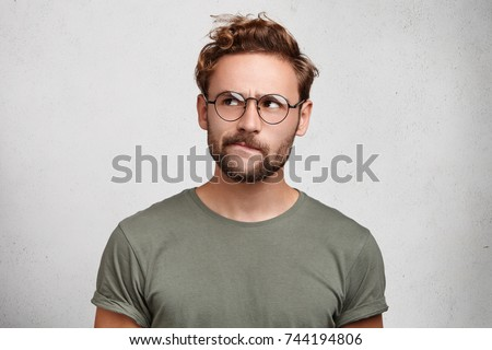 Serious thoughtful clever scientific worker wears spectacles, has beard, curves lower lip, tries to imagine new theory or thigs how to prove new axiom. Pensive unshaven man being very meticulous