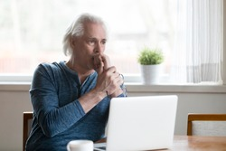 Serious thoughtful mature senior man looking away thinking of online problem solution near laptop, focused worried old middle aged male concerned feeling anxious or perplexed sitting with computer