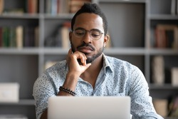 Serious thoughtful young african american business man looking at laptop screen working studying on computer focused on thinking of online problem search solution concentrate sit at home office desk