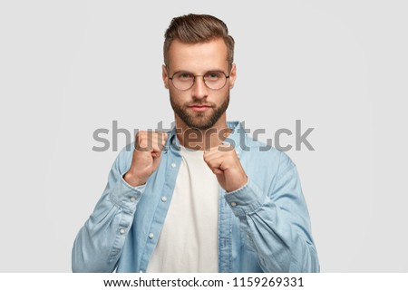 Serious unshaven young male shows fists, ready to defense himself, wears elegant blue shirt, spectacles, poses against white background. Confident bearded man fights with someone. Mens strength