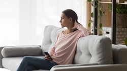 Serious upset lost on thoughts young woman looks out the window sitting alone on sofa in living room waiting call from boyfriend feels lonely, girl holding smartphone received unpleasant news concept