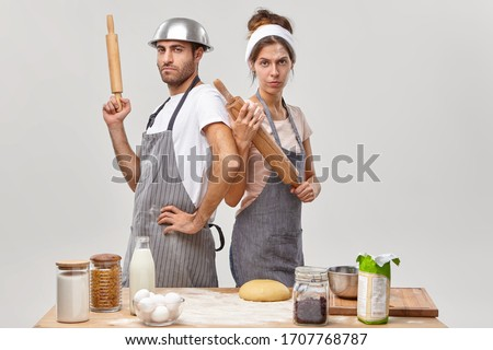 Serious woman and man stand back to each other, hold wooden rolling pins, participate in culinary battle, show who cooks better, compete in culinary arts, pose at kitchen. Cooking challenge.