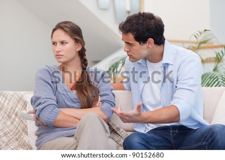 Serious woman being mad at her boyfriend in their living room - stock photo