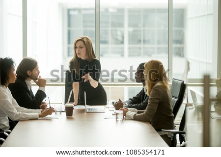 Serious woman boss scolding employees for bad results or discussing important instructions at multiracial team meeting, dissatisfied female executive talking to multiracial team at boardroom briefing