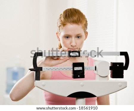 Serious woman checking dieting success by weighing herself on scale