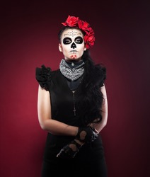 Serious woman in day of the dead mask on red