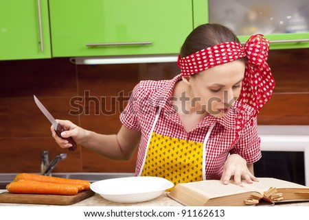 Serious woman in the kitchen with knife is reading recipe book