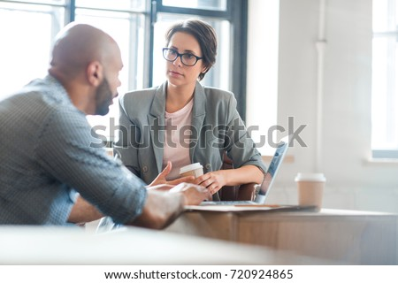 Serious woman listening to co-worker explaining new online business trends