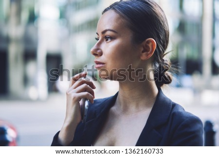 Serious woman looking away during free time on urban setting holding modern smartphone gadget in hand, millennial caucasian female economist with cellular phone feeling pondering on publicity area