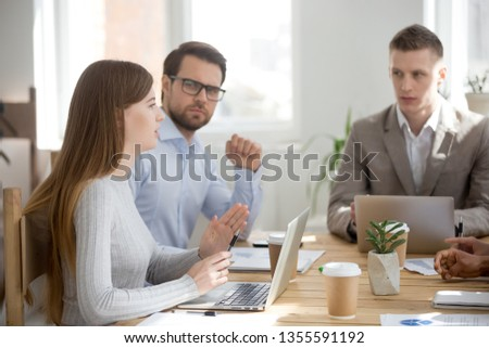 Serious woman talk at business meeting to colleagues and boss. Female worker express opinion, offer option, share ideas. Group of people sitting listening to speaker. Team work, team building concept