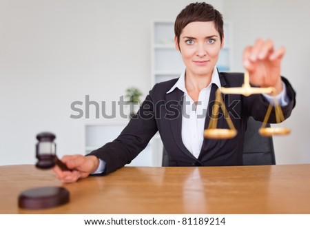 Serious woman with a gavel and the justice scale in her office