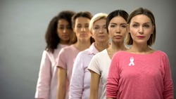 Serious women wearing pink breast cancer awareness ribbons standing in row