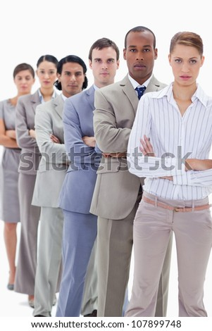 Serious workmates dressed in suits crossing their arms in a single line with focus on the first man