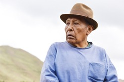 Serious wrinkled native american grandfather outside.