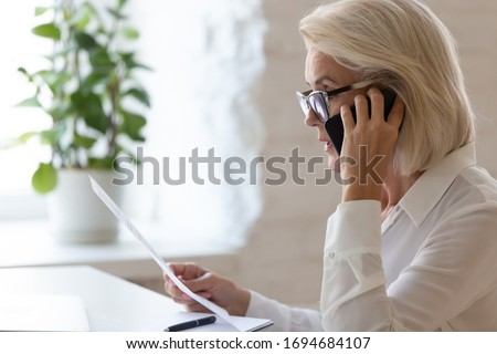 Serious 60 years old businesswoman talking on smartphone and reading document, solving corporate business problem. Female employee discussing document by cellphone, receive news.