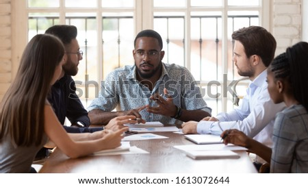 Serious young african American male ceo or boss lead office meeting with multiethnic colleagues, diverse coworkers gather in boardroom brainstorm discuss business ideas consider project together