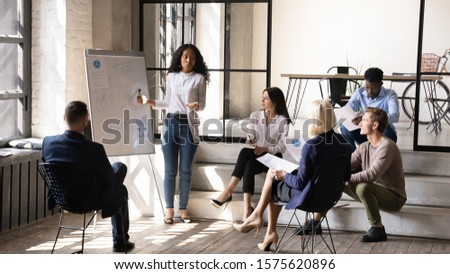 Serious young african ethnicity businesswoman trainer speaker presenting research results with charts on whiteboard, explaining company marketing strategy to diverse different generations colleagues.