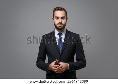 Serious young bearded business man in classic suit shirt tie posing isolated on grey background studio portrait. Achievement career wealth business concept. Mock up copy space. Holding mobile phone ストックフォト ©