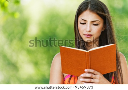 serious young, beautiful girl holding an open book, read background summer green park Stock photo ©