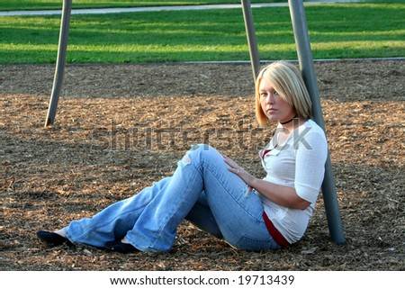 Serious young blond woman sitting on the ground in profile, her face turned to her left toward the viewer, while leaning back against a metal pole of a playground swing set.