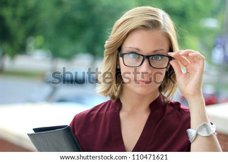 Serious Young Business Woman Wearing Eye Glasses Looking at the Camera