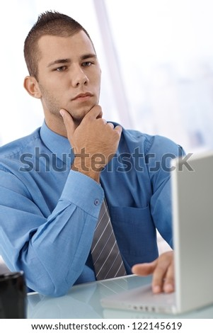 Serious young businessman at desk with laptop computer, thinking.