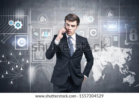 Serious young businessman in black suit talking on smartphone near concrete wall with infographics drawn on it. Concept of big data #1557304529