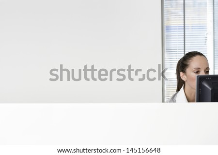 Serious young businesswoman using computer in office cubicle