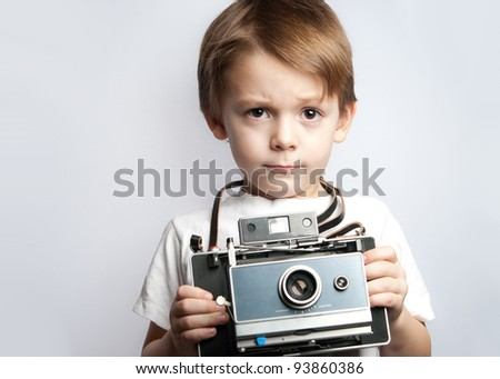 serious young child photographer holding a instant camera taking a picture on a white background #93860386