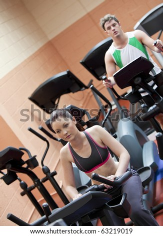 Serious young couple doing exercises using equipments in a sport centre - stock photo